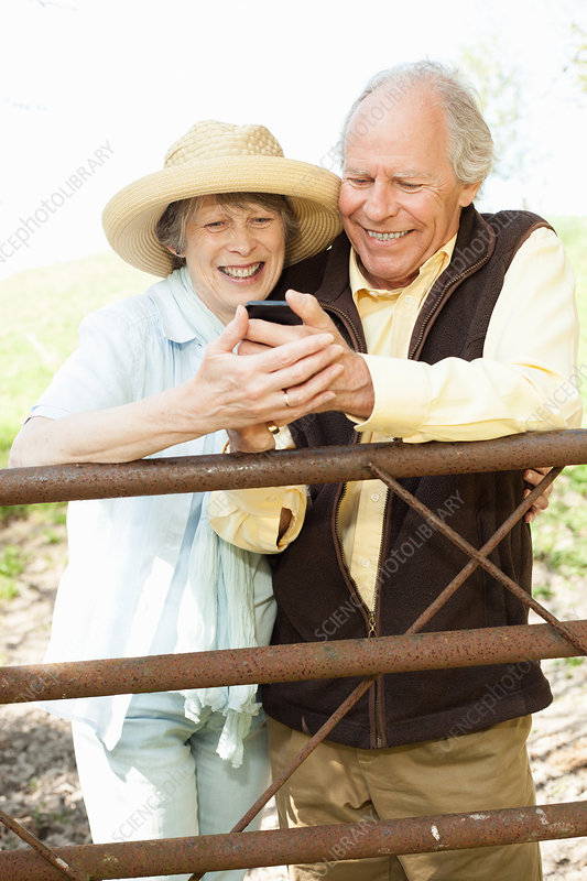 Couple smiling at message on mobile phone