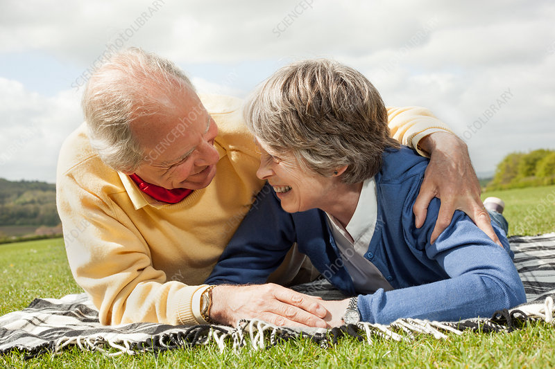 Husband and wife lying in field