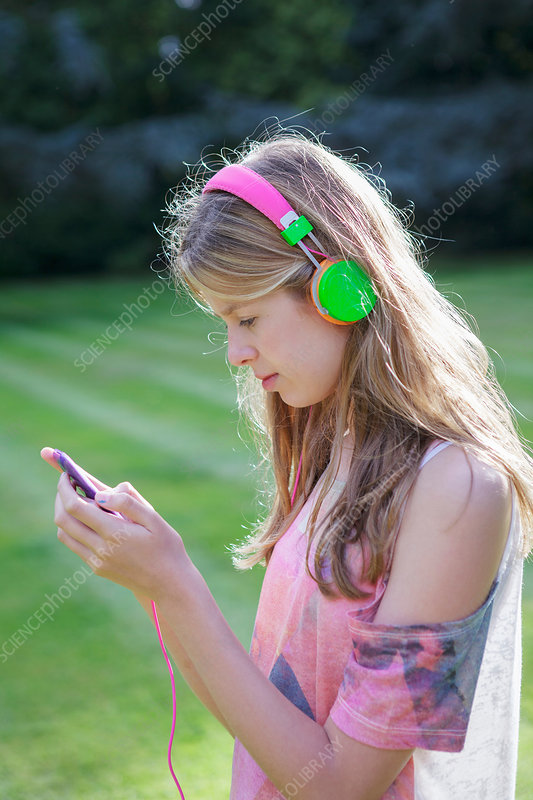Teenage girl listening to mp3 player