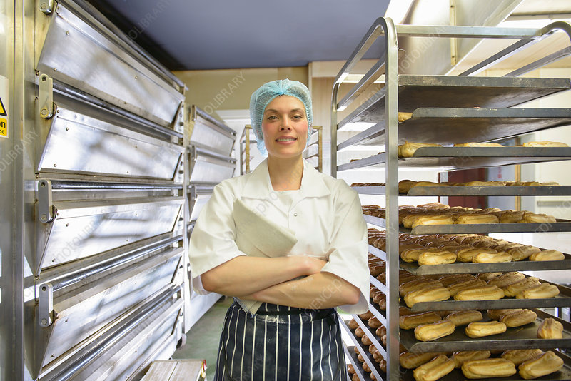 Baker standing by racks of baked pastries
