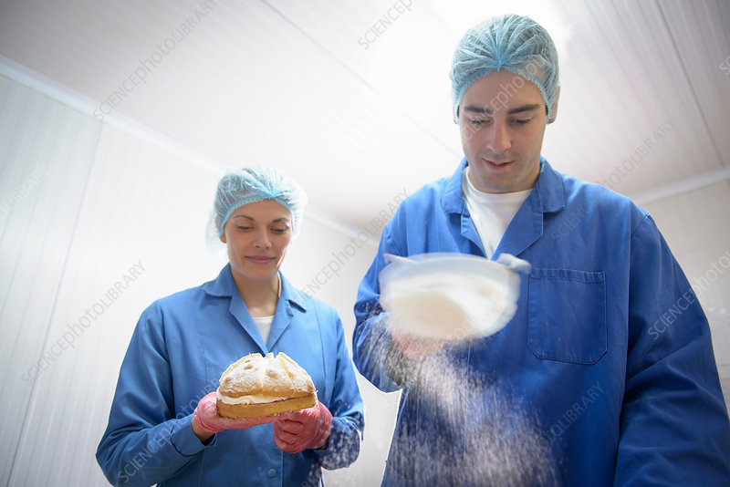 Bakers dusting sugar onto baked cakes