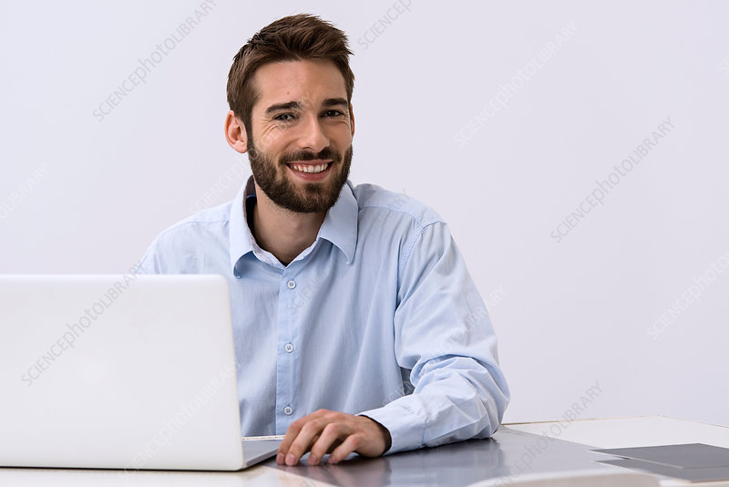 Young man sitting at desk with laptop
