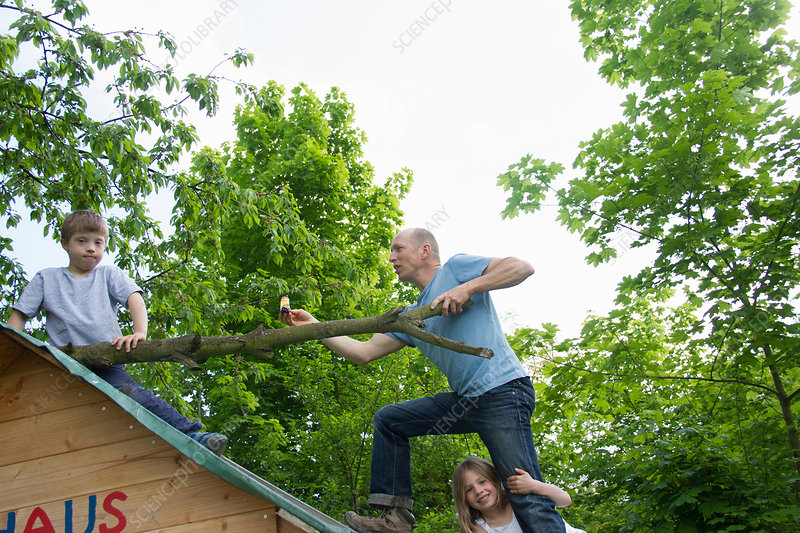 Father and children on playhouse roof
