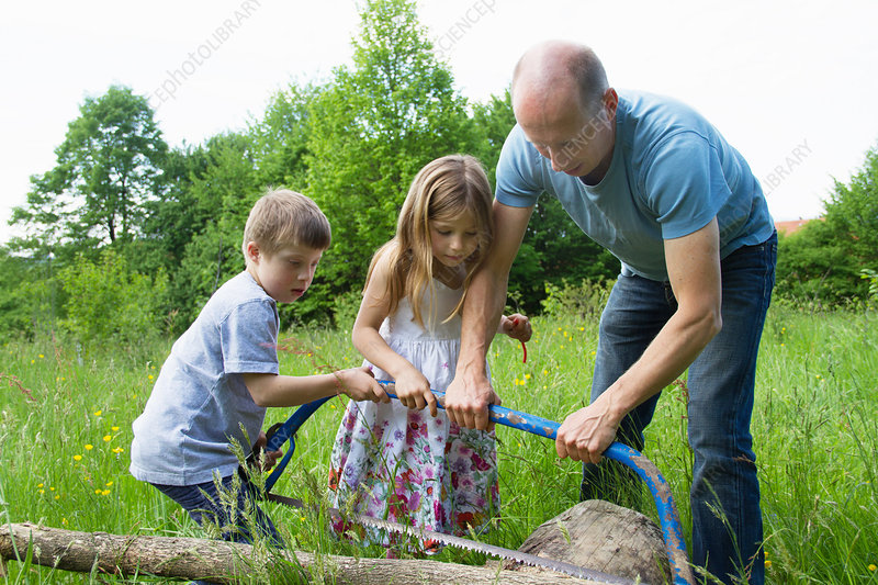 Father teaching children to use hacksaw