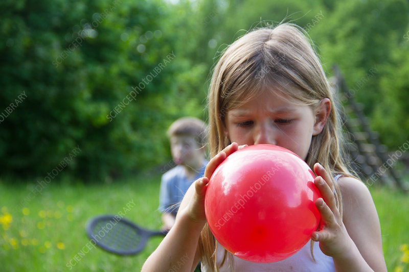 Girl blowing up red balloon