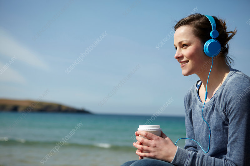 Woman at coast with coffee and earphones
