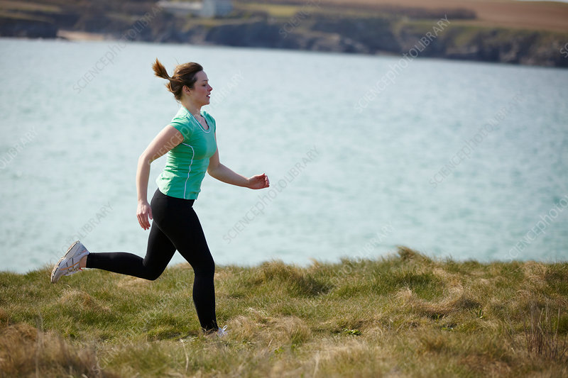 Young woman running near coast