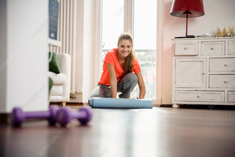Woman rolling up exercise mat at home