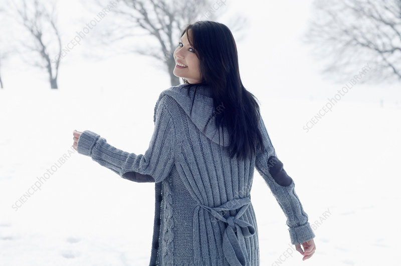 Young female walking in snowy field