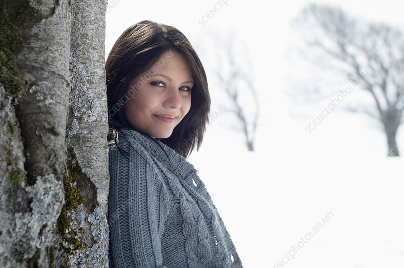 Female leaning against tree