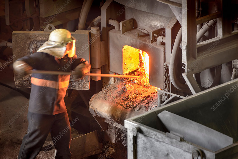 Steel worker poking furnace