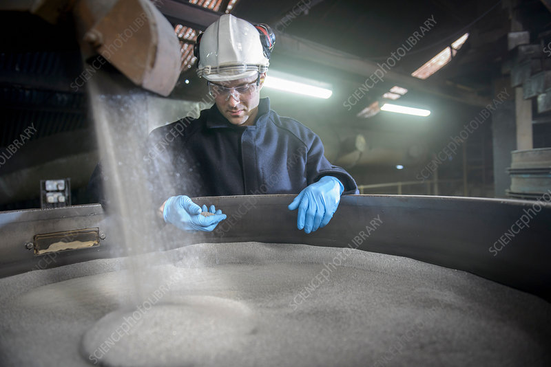 Worker checking container of steel shot