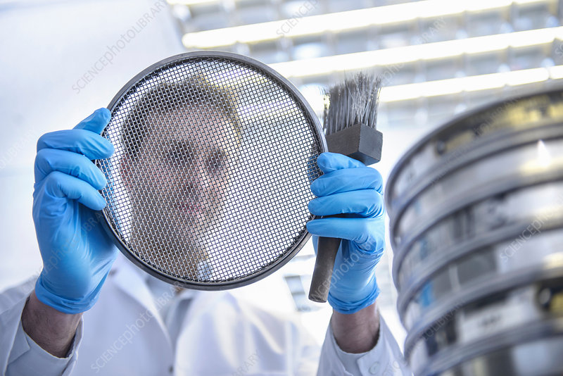 Scientist holding metal brush and sieve