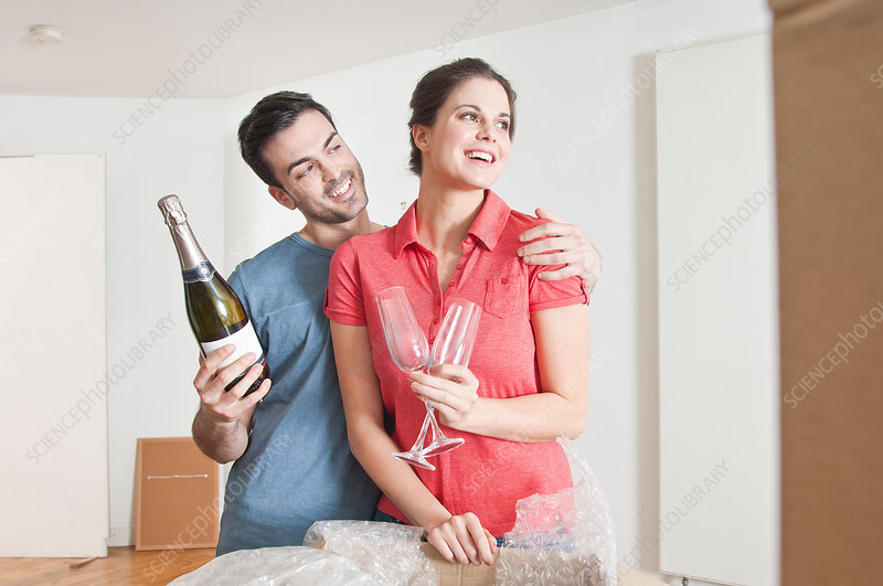 Couple celebrating move with champagne