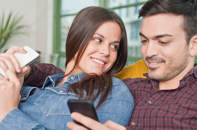 Young couple at home using mobile phones