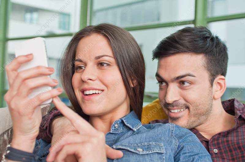 Young couple at home sharing mobile phone