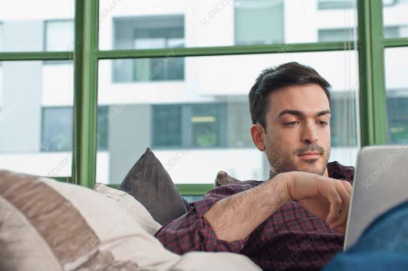 Young man at home using digital tablet