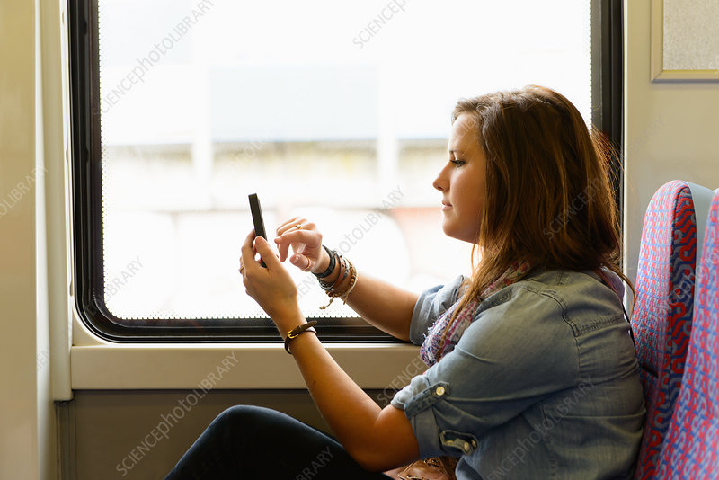 Female using smartphone whilst on train