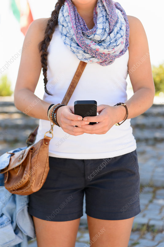 Woman standing in street using smartphone