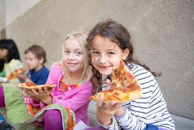 Children eating pizza outdoors
