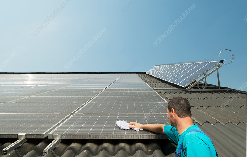 Farmer cleaning solar panels