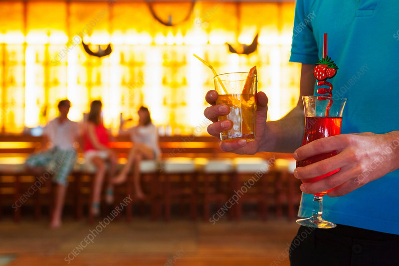 Young man carrying cocktails in bar