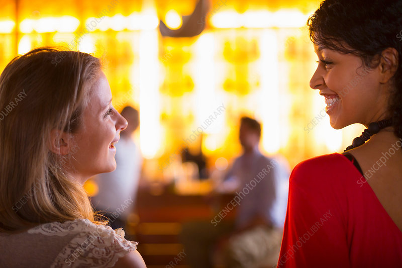 Two young females talking in bar