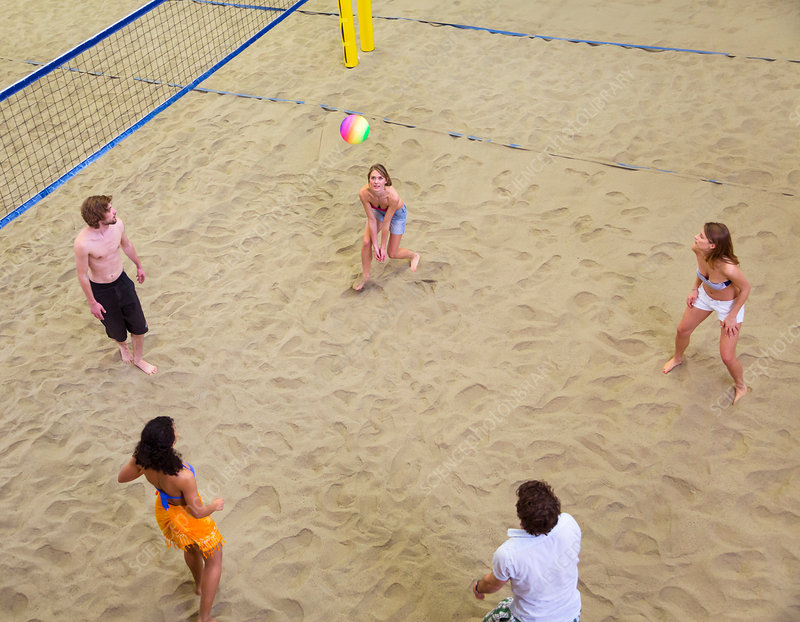 Friends playing indoor beach volleyball