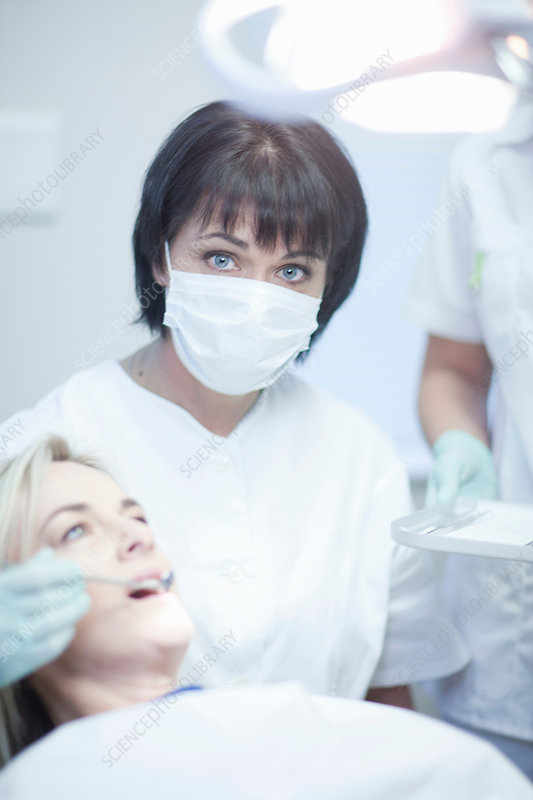 Dentist ready to treat female patient