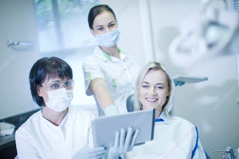 Dentist and patient looking at tablet