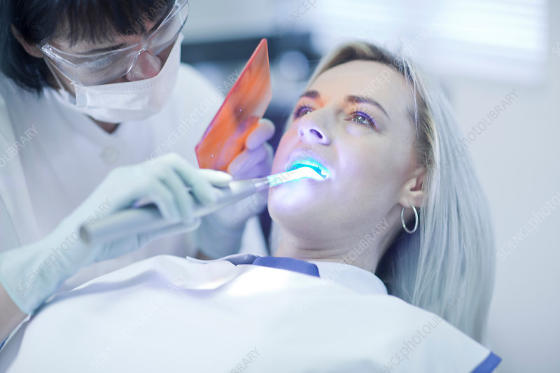 Dentist using UVlight on patient's teeth