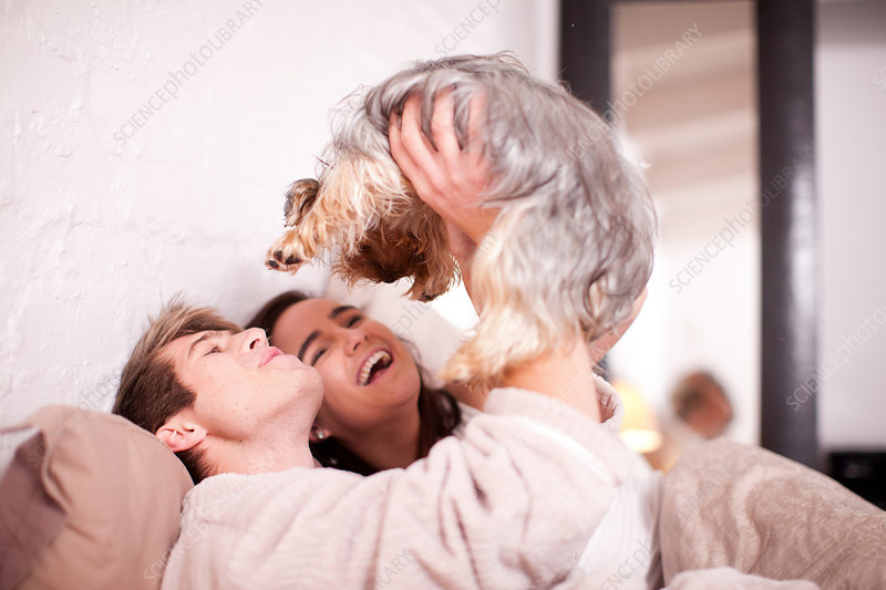 Young couple in bed with pet dog