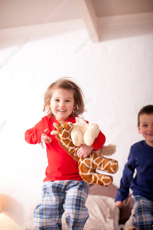 Two young children jumping on bed