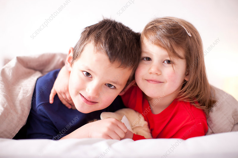 Two young children hugging under duvet