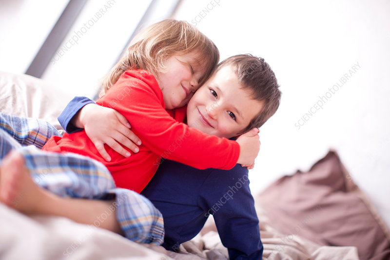 Two young children hugging on bed