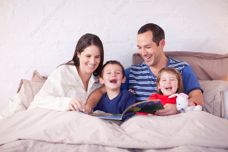 Family looking at picture book in bed