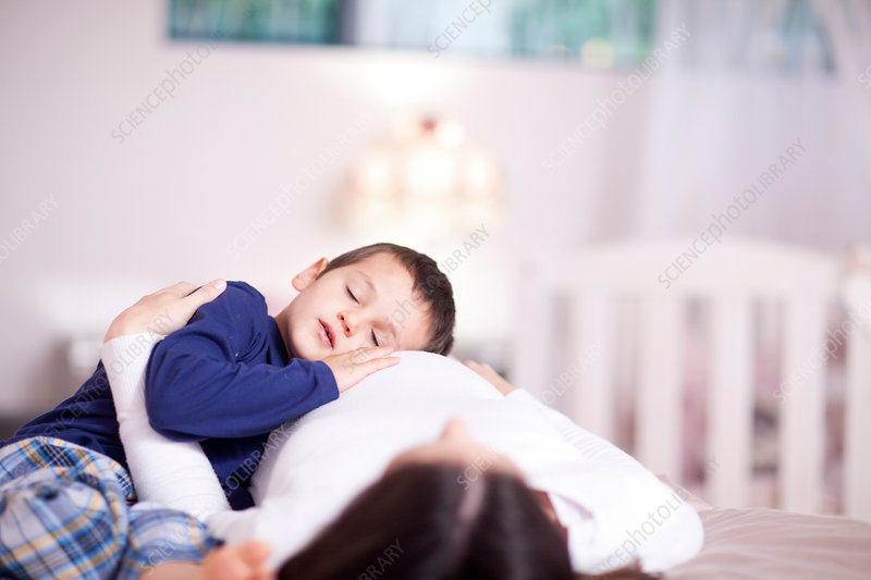 Boy quietly resting on his mothers bump
