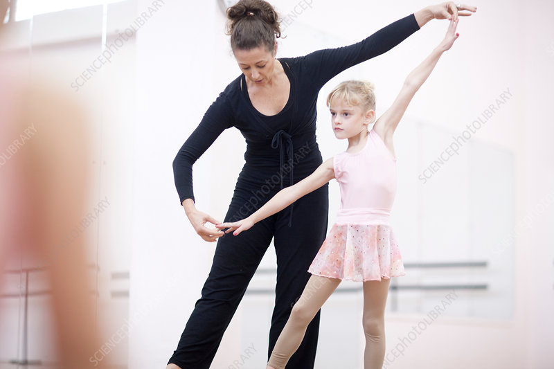 Ballerina practicing pose with teacher