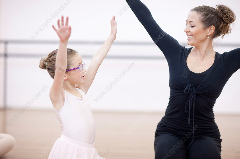 Young ballerina copying teachers pose