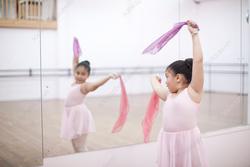 Young ballerina dancing with pink scarves