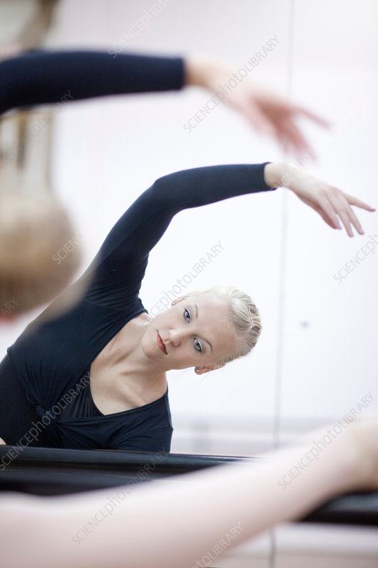 Female ballerina practicing at the barre