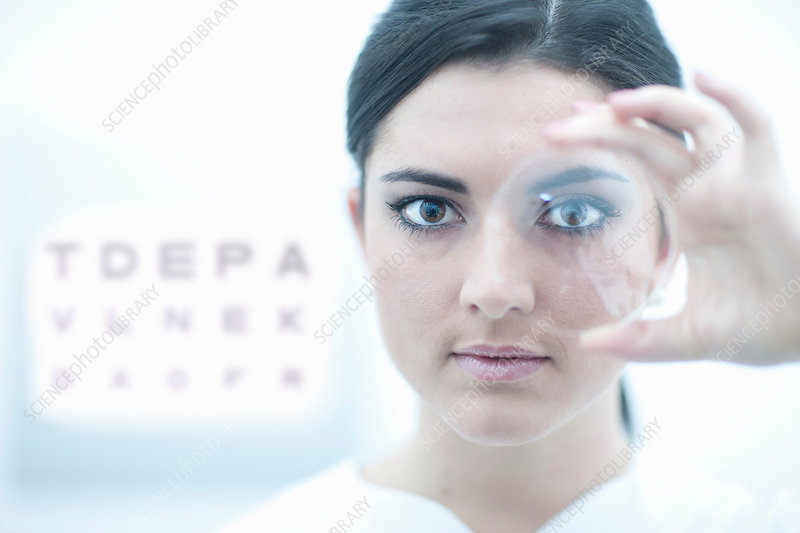 Optician holding lens in eye clinic