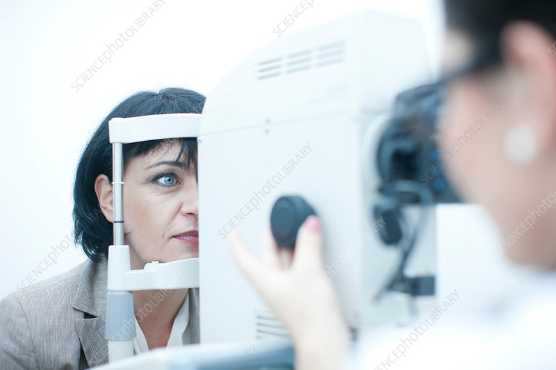 Optician monitoring patient in eye clinic