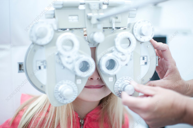 Optician testing young girl in eye clinic