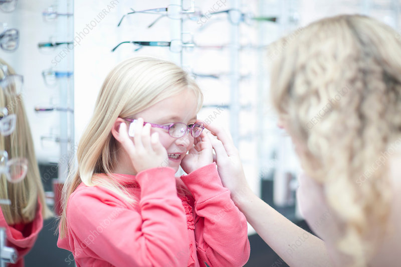 Young girl trying on eyeglasses
