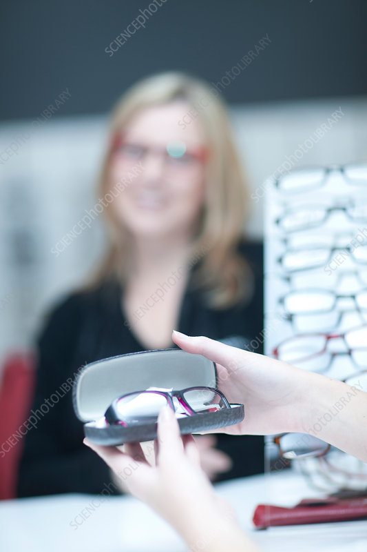 Shop assistant showing customer glasses