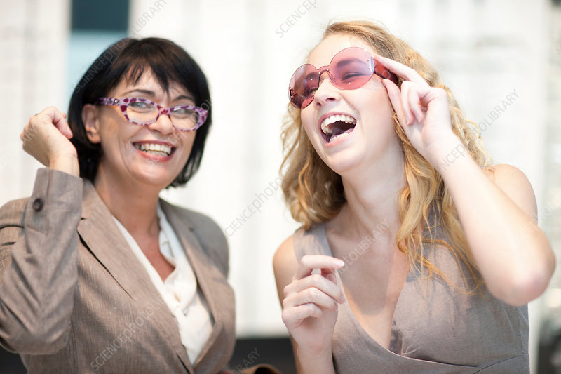 Women laughing whilst trying on glasses