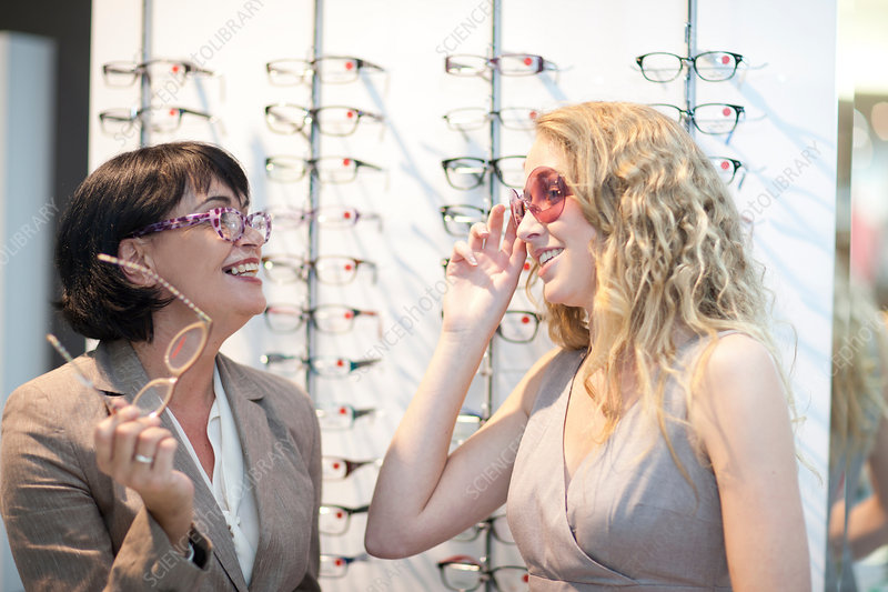 Women trying on glasses in opticians shop