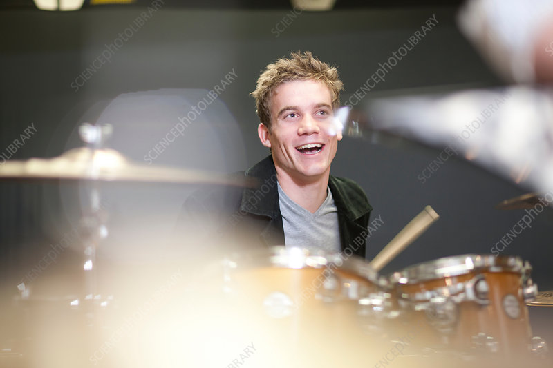 Young male playing drum kit