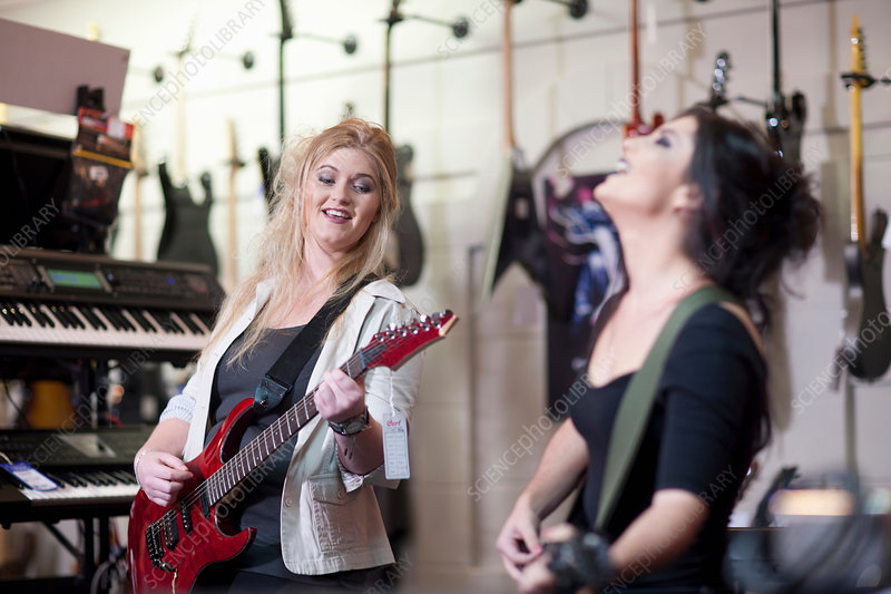 Two young women trying electric guitars